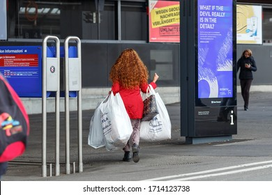 ZUERICH, SWITZERLAND - NOVEMBER 9, 2019. Young red-haired woman carrying many shopping bags after a big sale in front of Central Railway Station. City of Zuerich, Switzerland.