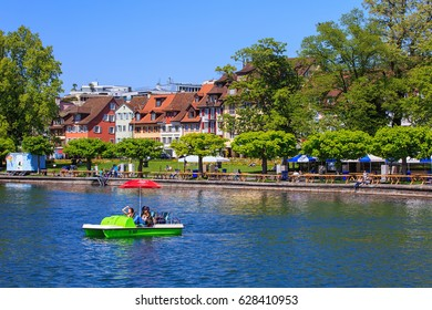 Zug, Switzerland - 6 May, 2016: people in a boat on Lake Zug and on the embankment of the lake, buildings of the city of Zug in the background. Lake Zug is a lake in central Switzerland.