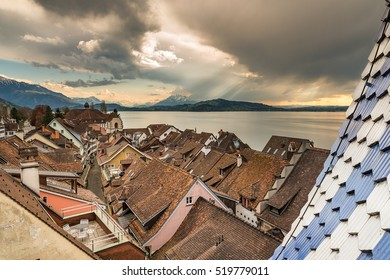 Zug, Switzerland. Aerial View orange roof medieval cityscape old town, Lake and clock tower in Zug town near Zurich city in Switzerland under golden sunset dramatic sky in summer