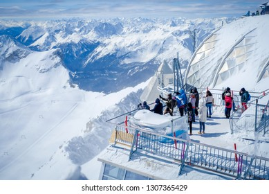 Zugspitze, Germany - April 1, 2018 : People standing on observation deck at the top of Zugspitze Mountain in the Alps, Germany