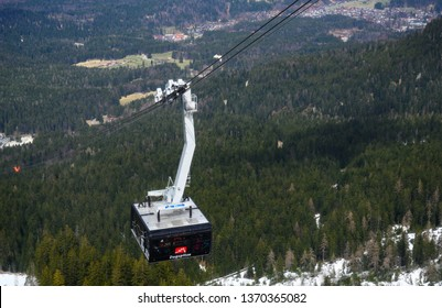 ZUGSPITZE, GERMANY, April 3, 2019: ropeway gondola or cable car with a lot of tourists is driving to the Zugspitze, the highest mountain in Germany in the Bavarian Alps, copy space