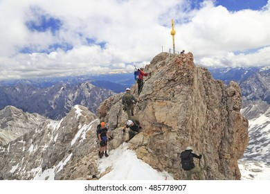ZUGSPITZE, GERMANY - JUNE 28, 2016: Hikers at the cross on the summit of Zugspitze Mountain, the highest in Germany.