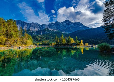 Zugspitze and the green and blue Eibsee in Germany at Sunset