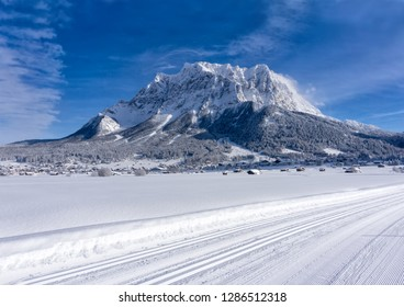 The Zugspitze Massif from the valley of Ehrwald in sunny winter day, groomed ski trails in foreground. Winter mountain landscape.