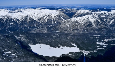 zugspitze mountain alpine beautiful scenic panorama. Panoramic snow alpen mountains at sunny winter with blue sky.  landscape with snowy peaks of the mountains and lake. Germany landmark