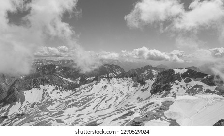 Zugspitze mountain is the highest place in Bavaria, Germany. Snowy peaks of the Alpine Mountains. View of the observation deck at the top of Zugspitze. Black and white photography.