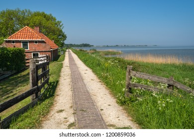 Zuiderzee museum, Enkhuizen, The Netherlands - May 9, 2019 : A gravel village road on the top of the borders of the Ijsselmeer (called Zuiderzee in the past)