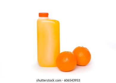 Zumo de naranja natural embotellado junto a dos naranjas sobre fondo blanco
