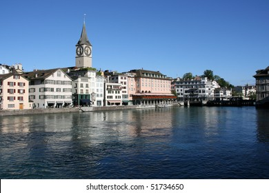 Zurich cityscape. St. Peter's Church tower with world's largest church clock face. Swiss city. Limmat river connecting with Lake Zurich.