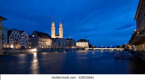 Zurich panorama at dusk, Grossmuenster and Munsterbrucke dominant, Switzerland