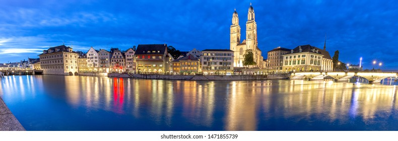 Zurich. Panoramic view of the city embankment and the church Grossmunster at sunset.