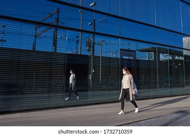 Zurich, Switzerland 05/04/2020: Young woman walking on a sunny day, wearing medical face mask, her reflection on a modern glass building