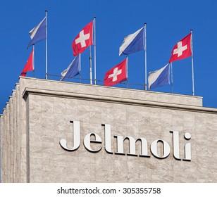 Zurich, Switzerland - 11 February, 2015: upper part of the Jelmoli building decorated with flags of Switzerland and Zurich. Jelmoli is a department store in Zurich.