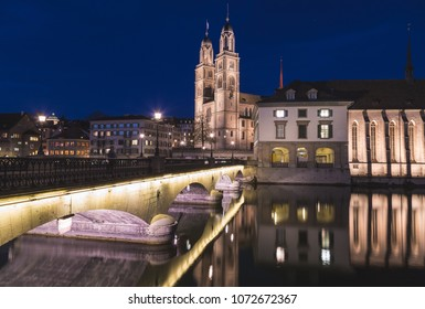 ZURICH, SWITZERLAND - 17TH APRIL 2018: The Grossmunster Church in Zurich from across the Limmat River at night.