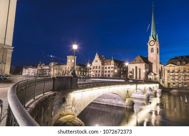 ZURICH, SWITZERLAND - 17TH APRIL 2018: The Fraumunster Church in Zurich from across the Munsterbrucke at night.