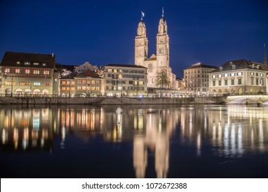 ZURICH, SWITZERLAND - 17TH APRIL 2018: The Grossmunster Church and Limmatquai street in Zurich from across the Limmat River at night.