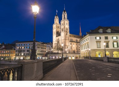ZURICH, SWITZERLAND - 17TH APRIL 2018: The Grossmunster Church in Zurich from across the Munsterbrucke at night.