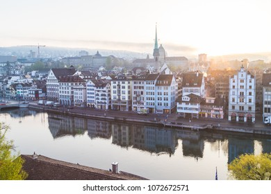 ZURICH, SWITZERLAND - 17TH APRIL 2018: A view of the Zurich skyline from the Lindenhof at sunrise. Architecture can be seen along the Limmatquai street.