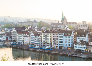 ZURICH, SWITZERLAND - 17TH APRIL 2018: A view of the Zurich skyline from the Lindenhof at sunrise. Architecture and trams can be seen along the Limmatquai street.