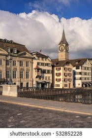 Zurich, Switzerland - 26 November, 2013: old town buildings, clock tower of the St. Peter Church in the background - view from the Munsterbrucke bridge. Zurich is the largest city in Switzerland.