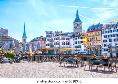 ZURICH, SWITZERLAND - APRIL 12, 2017:  People relax on benches and in street cafe on Limmat River quay in background of old buildings and Fraumunster church on sunny spring day, Zurich, Switzerland