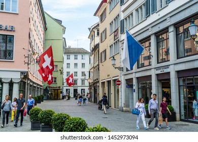 Zurich, Switzerland- April 28, 2018:  Street view of old town of Zurich at the bank of Limmat River, with national flag of Switzerland haning over the street.