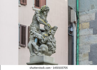 Zurich, Switzerland- April 29, 2018: Samson statue in front of a beautiful facade of a building. Street view of Old city of Zurich with a fountain in Switzerland
