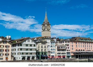Zurich, Switzerland- April 29, 2018: View of bank of Limmat River, with the clock tower of St. Peter Pfarrhaus and view of old town of old town of Zurich.