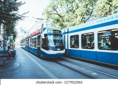 ZURICH, SWITZERLAND - AUG 23, 2018: A tram drives down the center of Bahnhofstrasse while people walk on the sidewalks in Zurich City, Switzerland.