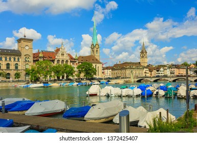 Zurich, Switzerland - August 1, 2016: boats on the Limmat river, buildings along the river, clock towers of the Fraumunster and St. Peter church. Zurich is the largest city in Switzerland.