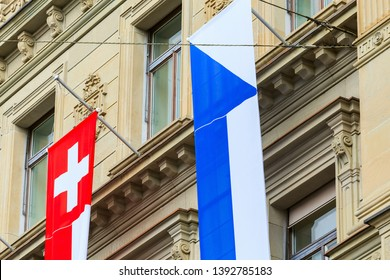 Zurich, Switzerland - August 1, 2016: part of the facade of the Credit Suisse building at Paradeplatz square decorated with flags of Zurich and Switzerland for the Swiss National Day celebration.