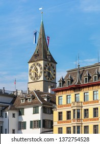 Zurich, Switzerland - August 1, 2018: tower of the St. Peter Church above buildings of the historic part of the city of Zurich. The medieval tower is a well-known sightseeing of the city of Zurich.