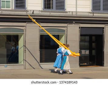 Zurich, Switzerland - August 1, 2018: two ladies carrying alpine horns passing along a street in the old town of city of Zurich to participate in the parade devoted to the Swiss National Day.