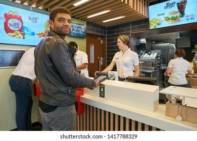 ZURICH, SWITZERLAND - CIRCA OCTOBER, 2018: a man pay order at McDonald's restaurnat in Zurich.
