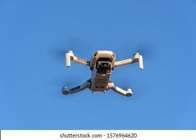 Zurich, Switzerland - December 01, 2019: DJI Mavic Mini drone in the air against the blue sky