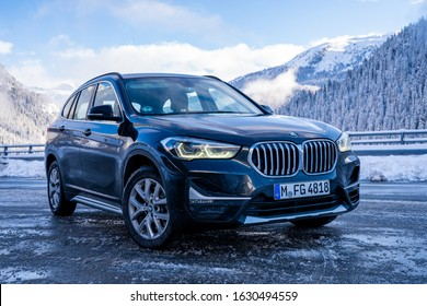 Zurich, Switzerland. January 10, 2020.  Brand new black BMW X1 SUV 2020 parked in Switzerland by the highway with beautiful winter mountains in the background.