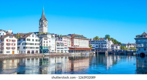 Zurich, Switzerland - July 10, 2016: View of the city center on the Limmat river with the St. Peter bell tower in the background