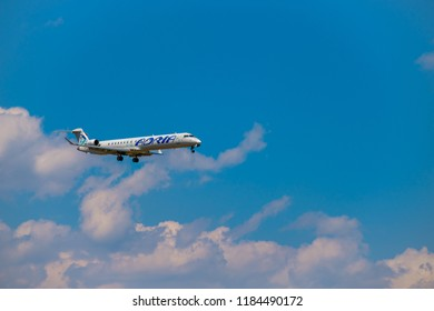 Zurich, Switzerland - July 19, 2018: Adria airlines airplane flying in the blue cloudy sky,  preparing for landing at day time in Zurich nternational airport