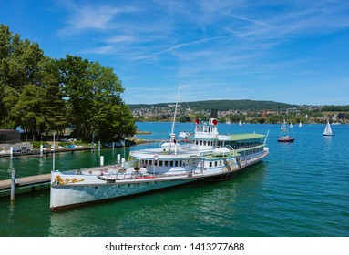 Zurich, Switzerland - June 1, 2019: Stadt Zurich steamboat at a pier on Lake Zurich, people in boats on the lake. The steamboat is owned and operated by the Lake Zurich Navigation Company.