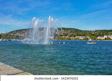 Zurich, Switzerland - June 1, 2019: a fountain on Lake Zurich, buildings of the city in the background. Lake Zurich is a lake in Switzerland, extending southeast of the city of Zurich.