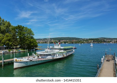 Zurich, Switzerland - June 1, 2019: Stadt Zurich steamboat at a pier on Lake Zurich, people in boats on the lake. The boat is owned and operated by the Lake Zurich Navigation Company.