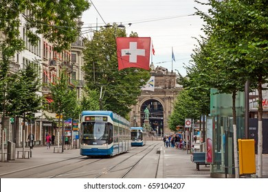 Zurich, Switzerland - June 10, 2017: Shopping promenade called Bahnhofstrasse, inner city of Zurich. Tram / train with swiss flag in front.
