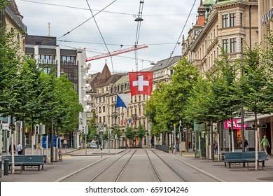 Zurich, Switzerland - June 10, 2017: Shopping promenade Bahnhofstrasse, inner city of Zurich. Swiss flag and tram railroad tracks in front.