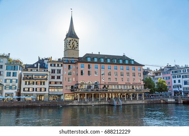 Zurich, Switzerland - June 10, 2017: Hotel Storchen at promenade Limmatquai, church Saint Peter in background