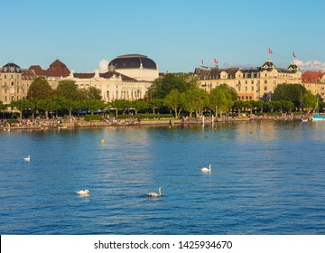 Zurich, Switzerland - June 16, 2019: Lake Zurich at sunset, people on its embankment, buildings of the city of Zurich in the background. Lake Zurich is a lake in Switzerland.