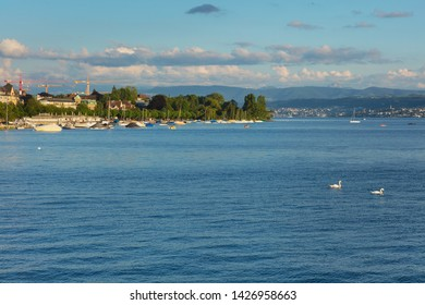 Zurich, Switzerland - June 16, 2019: Lake Zurich at sunset, people in boats, buildings of the city of Zurich, summits of the Alps in the background. Lake Zurich is a lake in Switzerland.