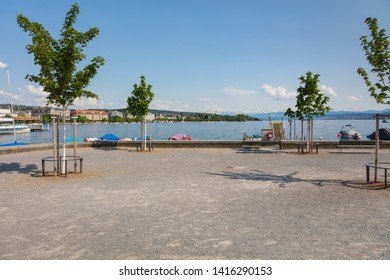 Zurich, Switzerland - June 4, 2019: embankment of Lake Zurich, summits of the Alps in the background. Lake Zurich is a lake in Switzerland, extending southeast of the city of Zurich.