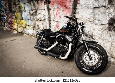 Zurich, Switzerland - March 2017: Black motorcycle 2017 Sportster Forty-Eight, motorbike Harley-Davidson with stone wall and graffiti in background