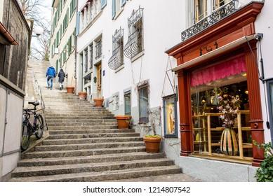 Zurich, Switzerland - March 2017: Couple walking in small medieval alley street in Zurich city centre, Switzerland