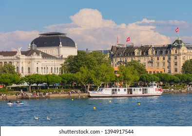 Zurich, Switzerland - May 11, 2018: people on the embankment of Lake Zurich in the city of Zurich, Opera House building in the background. Zurich is the largest city in Switzerland.